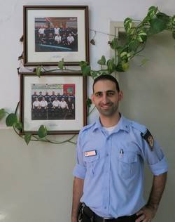 Fire fighter standing in front of photos